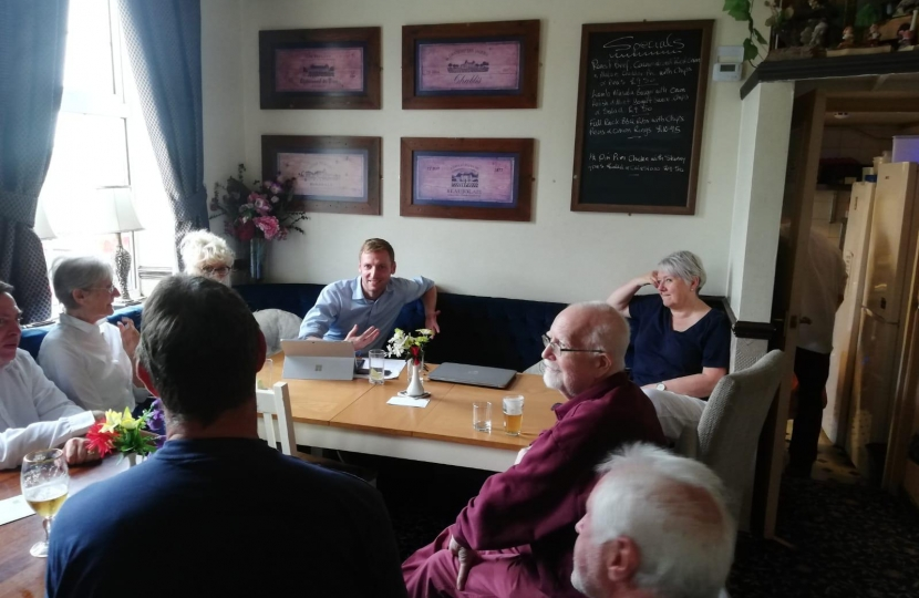 Lee Rowley at a table talking with residents